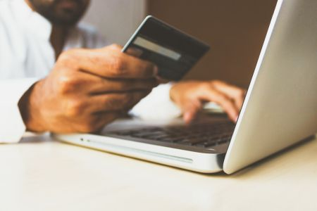 man holding credit card up beside computer